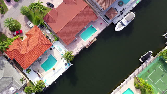 aerial top downward shot of canals flowing between houses in city, drone flying over boats - miami, florida - moving down stock videos & royalty-free footage