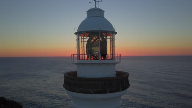vídeos de stock, filmes e b-roll de aerial: top of a lighthouse in beautiful sunset, byron bay, australia - farol estrutura construída