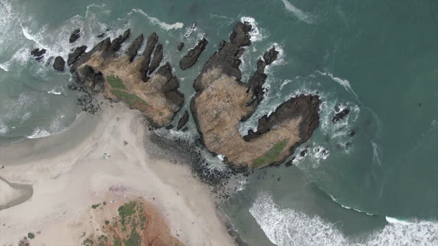 aerial top panning view of people by keyhole arch at pfeiffer beach, drone ascending over famous natural landmark splashing waves - big sur, california - natural landmark stock videos & royalty-free footage