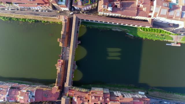 vídeos de stock e filmes b-roll de aerial top view: amazing famous ponte vecchio bridge over river arno - florence, italy - top view