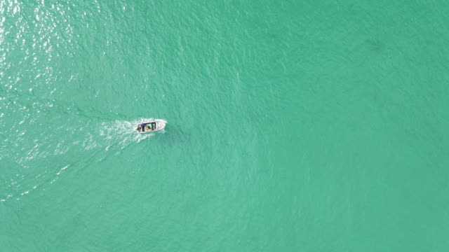 4k aerial top view, boat running on the sea - speed boat stock videos & royalty-free footage