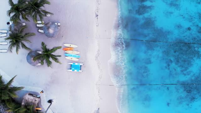 vídeos de stock e filmes b-roll de aerial top view: boats and sunbeds on beach under palm tree - enfoque de objeto sobre a mesa
