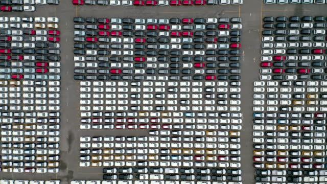 vidéos et rushes de entrepôt de voiture de vue aérienne à l'entrepôt d'attente de quai de chargement au navire de transporteur pour l'expédition dans le monde entier. - vendre