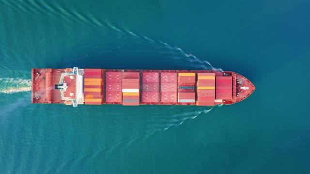 vidéos et rushes de navire de fret de conteneur de vue aérienne de dessus conduisant sur la mer pour le transport d'exportation d'importation d'importation logistique d'affaires ou le transport de fret. - cargo