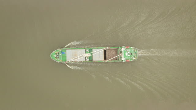 航空トップビューコンテナ貨物船は、ビジネスロジスティクス、輸入輸出、輸送または貨物輸送のためにターミナル商業港に行く美しい波のパターンでフルスピード。 - 引きずる点の映像素材/bロール