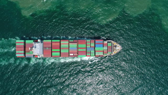 Aerial top view Container ship Full load container moving on the sea for logistics , shipping , import export or transportation.