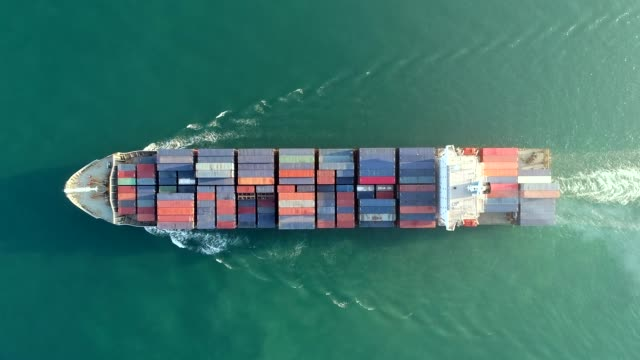 vídeos de stock e filmes b-roll de aerial top view container ship full load container on the green sea with beautiful wave pattern for logistics , shipping , import export or transportation. - barco