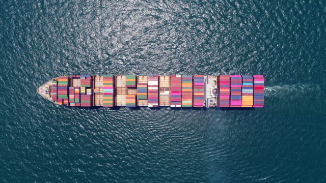 vídeos de stock e filmes b-roll de aerial top view container ship on deep blue sea for logistics , shipping , import export or transportation. - navio cargueiro