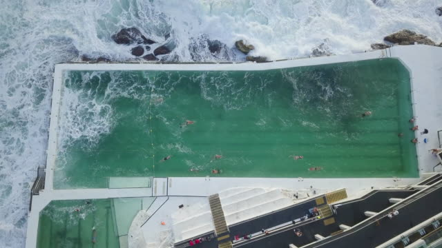 vídeos de stock, filmes e b-roll de aerial top view: huge wave crush into swimming pool of luxurious structure right by the ocean, bondi beach, australia - grande angular