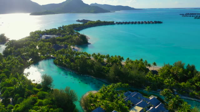 vídeos de stock e filmes b-roll de aerial top view of a beautiful tropical island in a bright blue lagoon, drone flying forward then slightly turning from left to right - bora bora, french polynesia - ilhas do pacífico