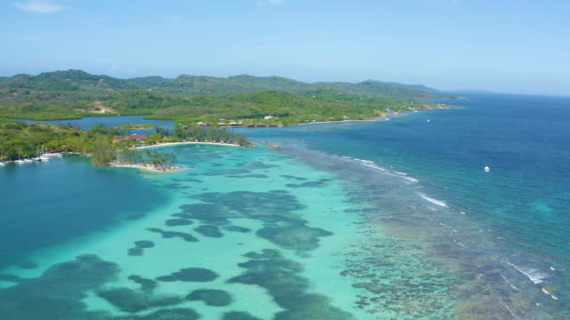 Aerial top view of a tropical island beach with white sand and emerald water in Roatan paradise island in the caribbean..