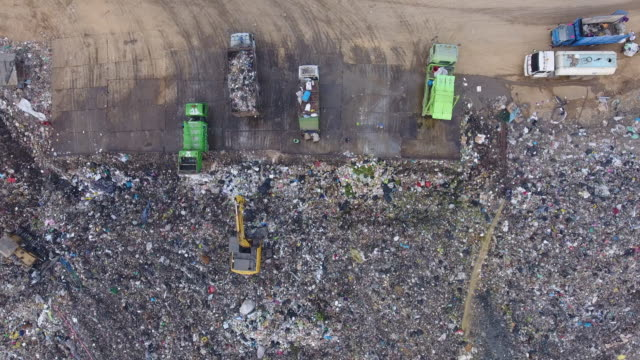 aerial top view of bulldozer and truck working on garbage hill - waste management stock videos & royalty-free footage