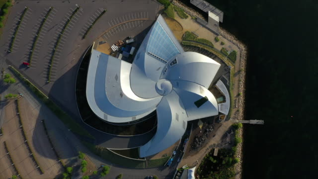 aerial top view of famous aquarium in city by sea on sunny day, drone circling over modern building - copenhagen, denmark - museum stock videos & royalty-free footage