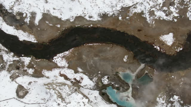 aerial top view of hot creek geological site amidst snow, drone panning over creek emitting steam during winter - mammoth lakes, california - mammoth lakes video stock e b–roll