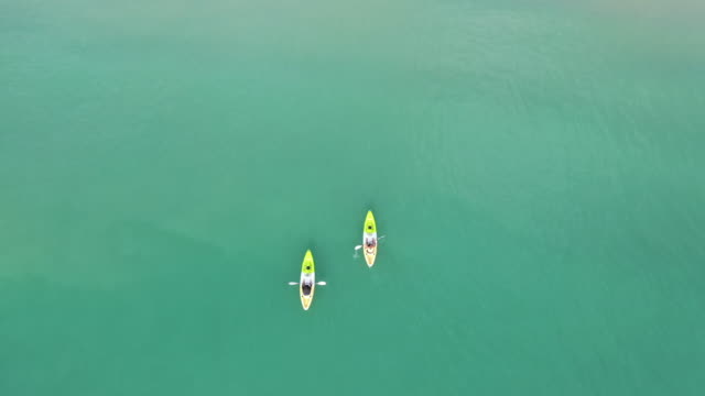 aerial top view of kayaking around sea with shade emerald blue water in sea of thailand - canoe stock videos & royalty-free footage