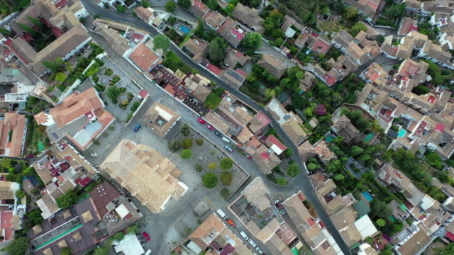 stockvideo's en b-roll-footage met aerial top view of mirador de san nicolas amidst buildings in city, drone panning over vehicles on street - granada, spain - table top view
