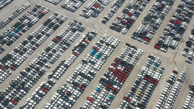 vídeos de stock e filmes b-roll de aerial top view of new cars lined up at industrial port. - aluguer de automóveis