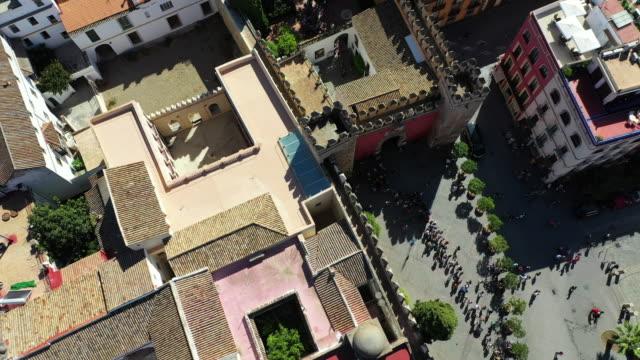 aerial top view of people at plaza del triunfo amidst buildings, drone ascending over tourists in city - seville, spain - top capo di vestiario video stock e b–roll