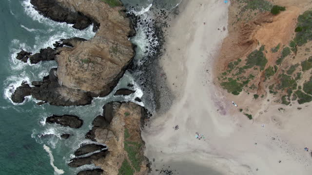 aerial top view of people by keyhole arch at pfeiffer beach, drone descending over famous natural landmark splashing waves - big sur, california - natural landmark stock videos & royalty-free footage