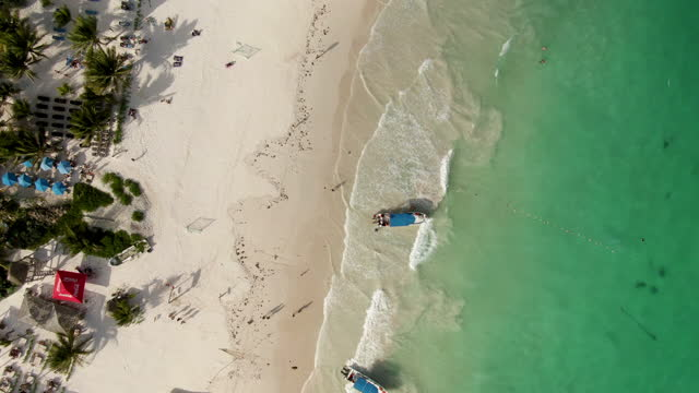 aerial top view of people enjoying sunny day at beach, drone ascending over boats on shore with turquoise water - tulum, mexico - tropical tree stock videos & royalty-free footage