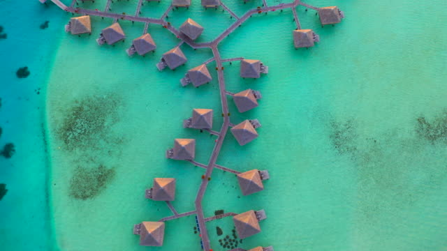 aerial top view of picturesque overwater bungalows, drone flying forward  - bora bora, french polynesia - bora bora stock videos & royalty-free footage