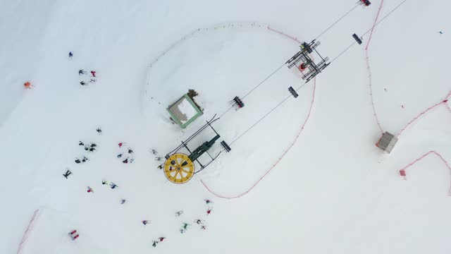 vídeos y material grabado en eventos de stock de aerial top view of ski lift for transportation skiers and snowboarders on snowy ski slope. drone flies over chair lift. ski resort. ski elevator cableway for people transportation on winter mountain. - centro de esquí