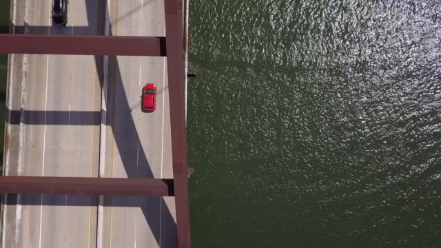 aerial top view of vehicles on arch bridge over river while drone flying on sunny day - austin, texas - arch bridge stock videos & royalty-free footage