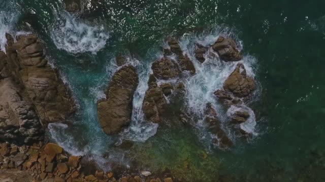 vidéos et rushes de aerial top view of waves splashing on rocks in sea during sunny day, drone ascending over rock formation - lloret de mar, spain - mar