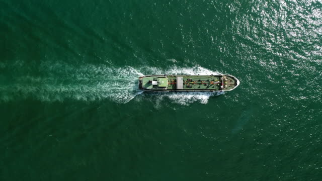 aerial top view oil ship tanker full speed with beautiful wave pattern going to refinery for load/unload for transportation. - motor oil stock videos & royalty-free footage