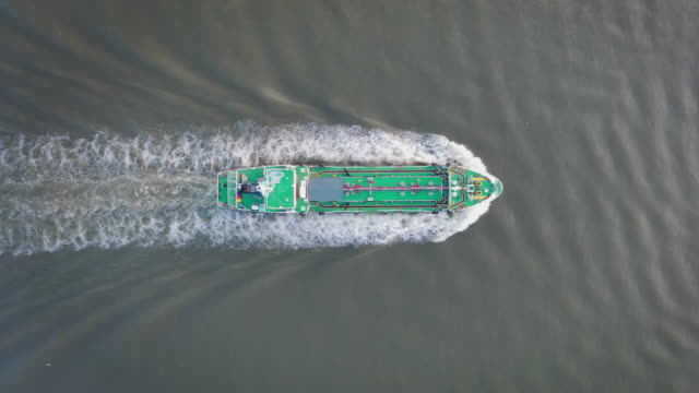 vidéos et rushes de aerial top view oil ship tanker full speed with beautiful wave pattern going to refinery for load/unload for transportation. - récipient