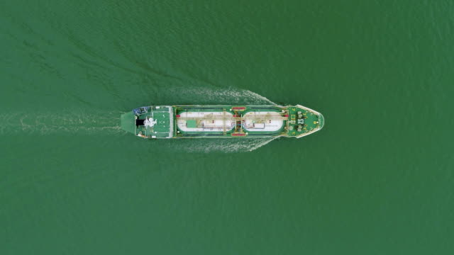vidéos et rushes de aerial top view oil ship tanker full speed with beautiful wave pattern going to refinery for load/unload for transportation. - tenir