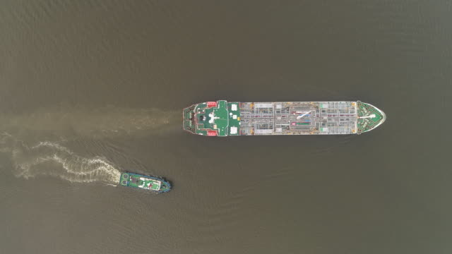 aerial top view oil ship tanker going to loading dock at refinery for load/unload for transportation. - industrial ship stock videos & royalty-free footage