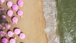 Aerial top view on the sandy beach. Pink umbrellas, sand, beach chairs and sea waves.