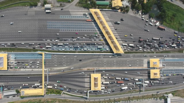 vídeos de stock e filmes b-roll de aerial top view over expressway toll gate with many vehicles passing through and pay fee - cabina de portagem