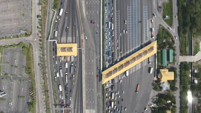 Aerial Top View Over Expressway Toll Gate with Many Vehicles Passing Through and Pay Fee