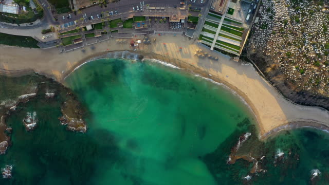 aerial top view shot of beach in city with turquoise sea at sunset, drone descending over coastline - jaffa, israel - jaffa stock videos & royalty-free footage