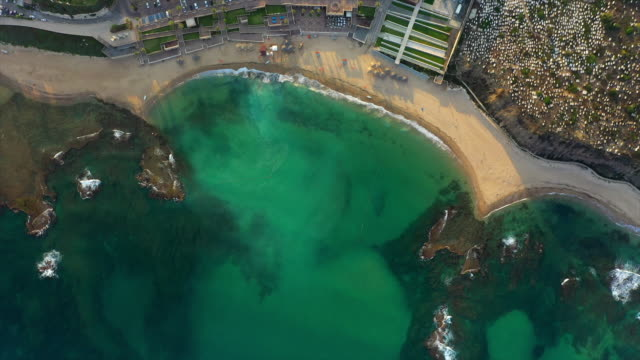 aerial top view shot of beach in city with turquoise sea during sunset, drone flying over coastline - jaffa, israel - jaffa stock videos & royalty-free footage