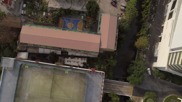 aerial top view shot of canal amidst buildings in city on sunny day, drone flying over vehicles on street - bangkok, thailand - top capo di vestiario video stock e b–roll