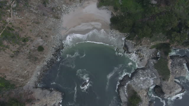 aerial top view shot of mcway falls splashing on shore at beach, drone ascending over famous natural landmark - big sur, california - natural landmark stock videos & royalty-free footage