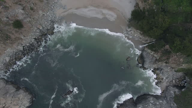 aerial top view shot of mcway falls splashing on shore at beach, drone descending over famous natural landmark - big sur, california - natural landmark stock videos & royalty-free footage