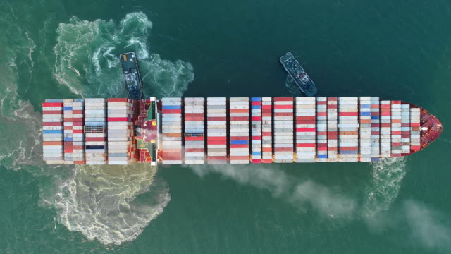 aerial top view tug boat drag container ship to sea port for shipping or transportation. - cargo ship stock videos & royalty-free footage