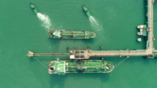 aerial top view tugboat drag oil tanker ship from refinery bridge for transportation on the sea. - compartment stock videos & royalty-free footage