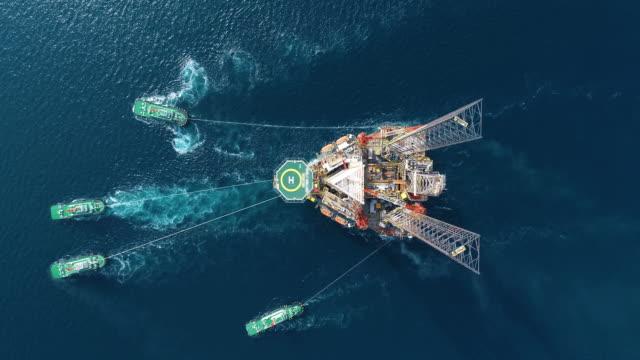 vidéos et rushes de le remorqueur aérien de vue supérieur traîne le navire de pétrolier du pont de raffinerie pour le transport sur la vidéo de stock de mer - faire le plein d'essence