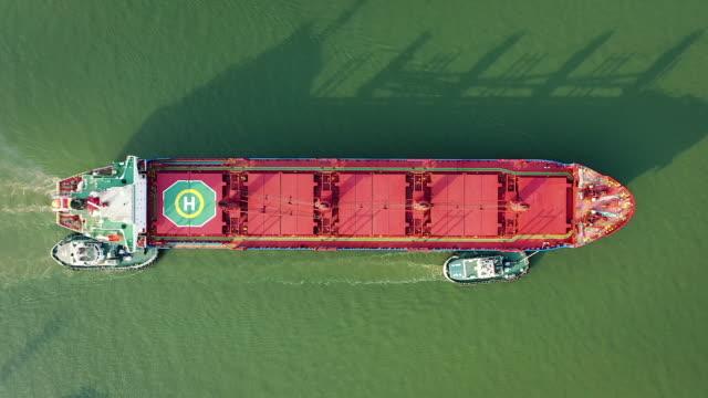 stockvideo's en b-roll-footage met luchttopmening sleepboot trekken leeg container vrachtschip dat zich aan kade bij de commerciële haven van terminal voor bedrijfslogistiek beweegt, de uitvoervan de invoer of het vervoer. - merchandise