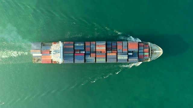 vidéos et rushes de aerial top view with zoom out : container ship full load container on the green sea for logistics , shipping , import export or transportation. - faire fonctionner