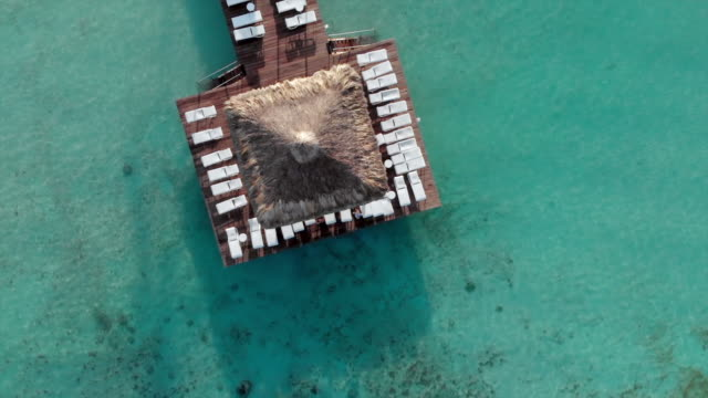 stockvideo's en b-roll-footage met aerial top view: wooden dock with white sunbeds under canopies on blue water - table top view