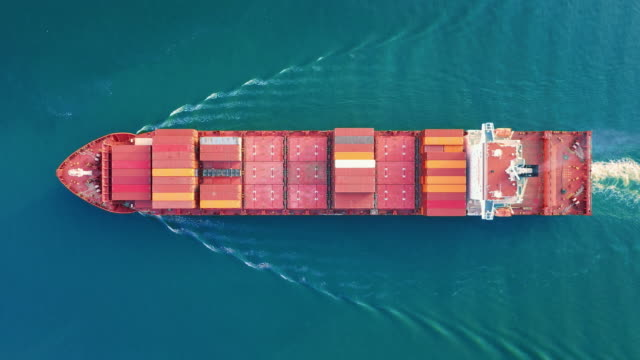 aerial top view zoom in container cargo ship full speed with beautiful wave pattern going to terminal commercial port for business logistics, import export, shipping or freight transportation. - cargo ship stock videos & royalty-free footage
