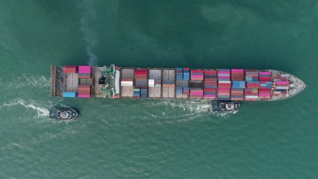 aerial top view zoom in tug boat drag container ship to sea port for logistics shipping, import export or transportation. - nautical vessel stock videos & royalty-free footage
