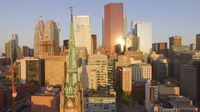 4k aerial toronto: pan view of modern downtown with historical church in the foreground at sunrise - toronto stock-videos und b-roll-filmmaterial