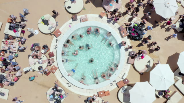 aerial: tourist relaxing in swimming pool at resort - ibiza, spain - illustration stock videos & royalty-free footage